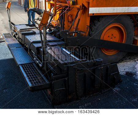 close-up details of industrial machinery working with asphalt mixing bitumen with hot asphalt layering on the road surface