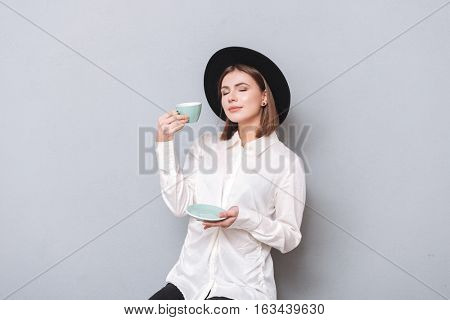 Portrait of a young pleased woman in hat sitting and drinking tea with eyes closed isolated on the gray background