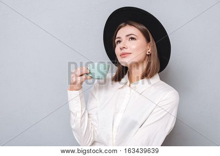 Close up portrait of a young wondering woman in hat drinking tea and looking away isolated on the gray background