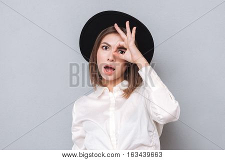 Portrait of a surprised astonished woman in hat looking through fingers isolated on a gray background