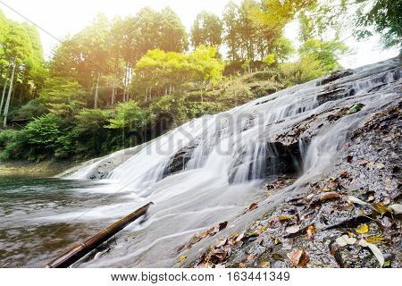 Japan travel concept - beautiful yoro keikoku valley waterfall under dramatic sun glow and morning blue sky in Chiba Prefecture Japan
