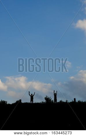 Silhouette of a standing photographer over blue sky in a landscape