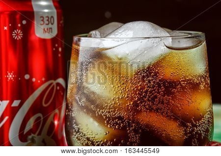 MINSK, BELARUS-DECEMBER 29, 2016: Can and glass of Coca-Cola with ice on dark wooden background. Coca-Cola is a carbonated soft drink sold in stores and vending machines throughout the world.
