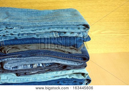 Many folded colored jeans on cupboard shelf, front view close-up