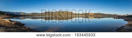 Panoramic view at dawn across a mirror calm Lac de Codole at Regino in the Balagne region of Corsica with clear blue sky