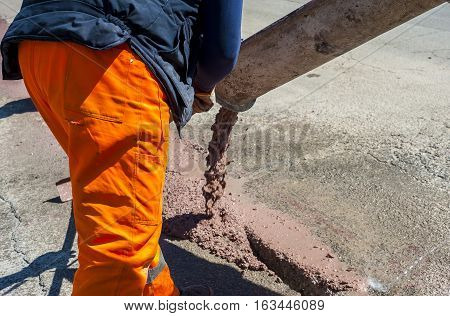 fiber optic cables buried in a micro trench with concrete colored red by a worker