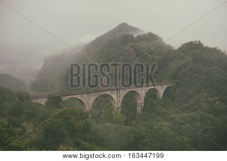 The old stone arch railroad bridge in the Tuscan hills covered by forests in the fog in the rain