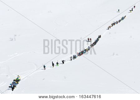 KAMCHATKA PENINSULA RUSSIAN FEDERATION - MARCH 9 2014: Group of sportsmens - skiers and snowboarders climbing the mountain for freeride. Competition Kamchatka Freeride Open Cup on Far East Russia.