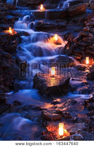 Cascading waterfall with multiple candles sitting on the rocks at twilight