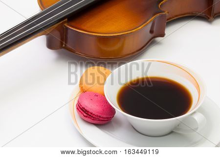 Music break - Old violin cup of coffee and traditional french colorful macarons on the white table