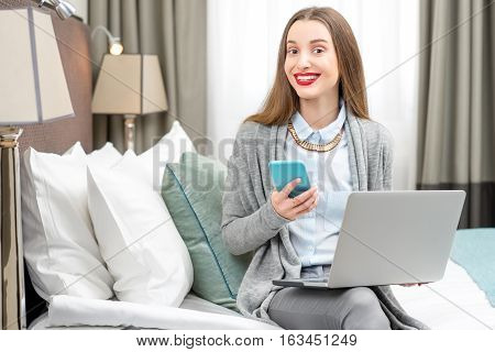 Business woman sitting with laptop in the luxury hotel room. Staying at the hotel during the business trip
