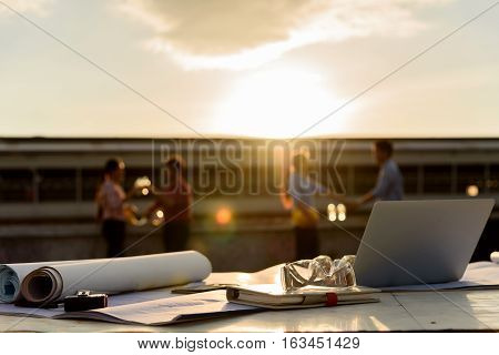 Several of construction design tools with blurred of Engineers relaxing and talk about project after working time in background