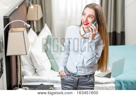 Young business woman talking with phone in the hotel. Calling to the concierge service from the hotel room