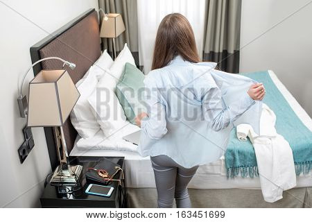 Young tired business woman undressing after working day in the hotel room