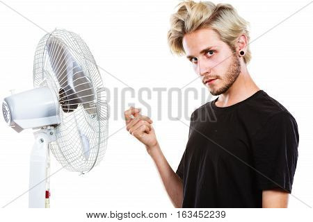 Air conditioning heat artistic concept. Young man in front of cooling fan artistic way studio shot isolated.