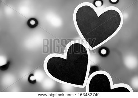 Several black hearts photographed against a lit background photographed in black and white