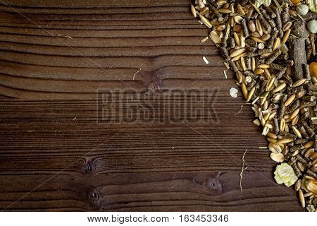 dry food for rodents on dark wooden background top view.