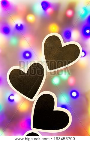 Three black hearts with white border against a lit background