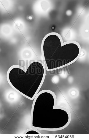 Three black hearts against a lit background photographed in black and white