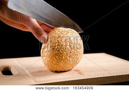 Cutting the buns with sesame seeds with a kitchen knife on wooden board, black background