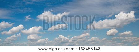 wide blue panoramic sky with fluffy cumulus clouds