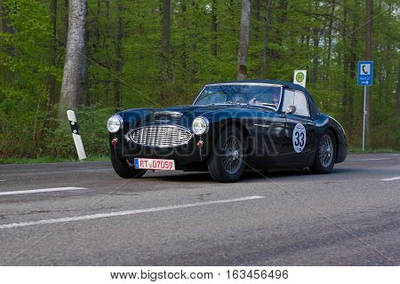 HEIDENHEIM GERMANY - MAY 4 2013: Norbert Odparlik and Birgit Odparlik in their 1958 Austin Healey 100 BN4 at the ADAC Wurttemberg Historic Rallye 2013 on May 4 2013 in Heidenheim Germany.