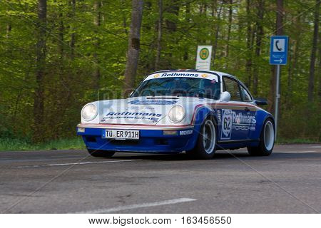 HEIDENHEIM GERMANY - MAY 4 2013: Ernst Richter and Annette Friess in their 1981 Rothmans Porsche 911 at the ADAC Wurttemberg Historic Rallye 2013 on May 4 2013 in Heidenheim Germany.