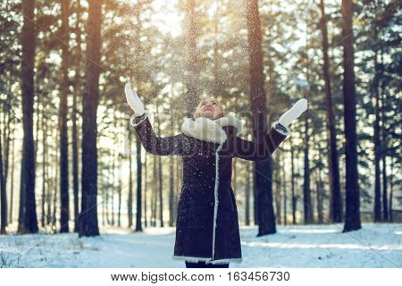 Attractive Woman Throws Up Snow Into The Air At Sunset