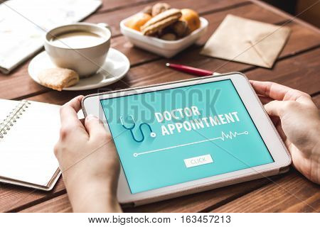 concept of appointment to doctor online on wooden background