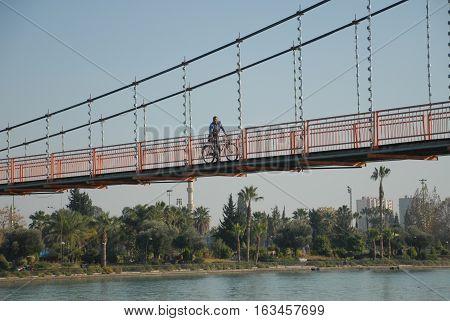 ADANA/TURKEY-DECEMBER 9, 2016:  Cyclist on the suspension bridge over the Seyhan River of Adana. December 9, 2016-Adana/Turkey