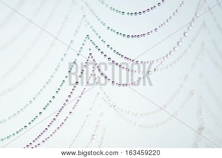 Close up of a spider web with dew drops on a light blue background