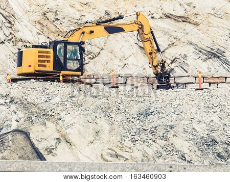 Industry. Heavy duty excavator machine digger bulldozer working on stone construction site Norway Scandinavia