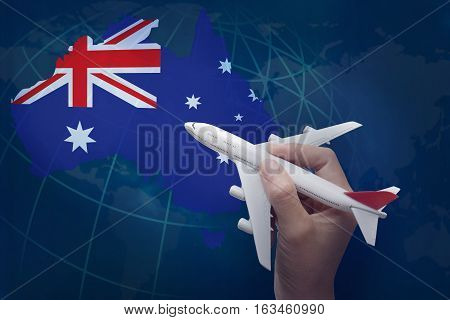 hand holding airplane with map of Australia.