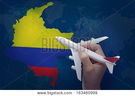 hand holding airplane with map of Colombia.