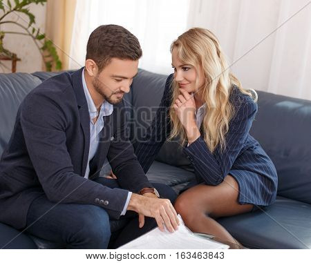 Blonde businesswoman seducing rich young businessman in office