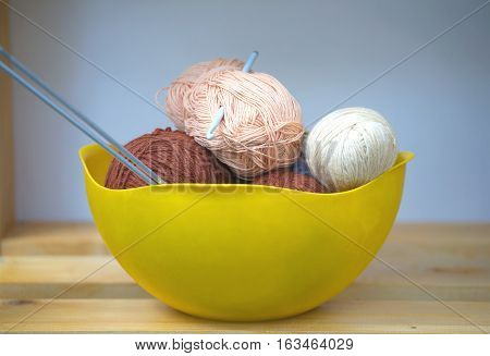 Color skeins of wool yarn, knitting needles and crochet hook in a big yellow bowl on wooden shelf. Photo closeup