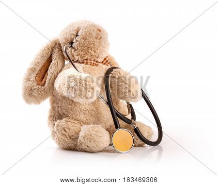 pediatrician concept - toy rabbit with stethoscope on white background
