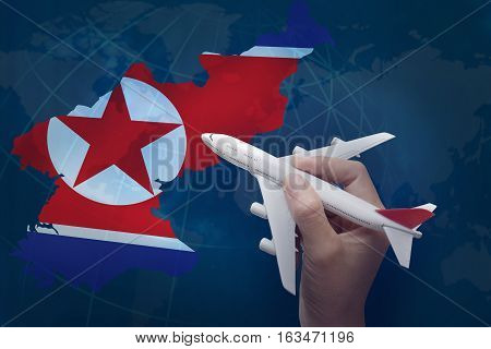 hand holding airplane with map of North Korea.
