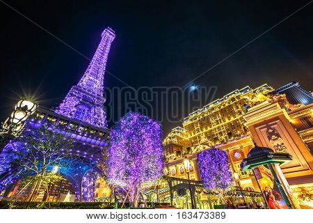 Macau, China - December 8, 2016: the spectacular blue and purple Macau Eiffel Tower, icon of The Parisian, a luxury Resort Hotel Casino in Cotai Strip owned by Las Vegas Sands, shines bright of night.