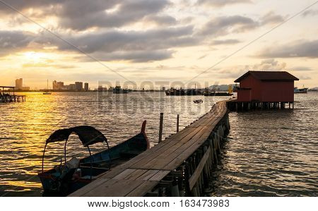 Sunrise on jetty with urban skyline on the opposite seashore Georgetown city Penang Island Malaysia