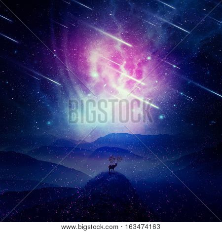 Majestic deer with long horns as tree branches stand on the peak of a rocky valley below a wonderful night sky with falling stars and sparkles. Mystic wildlife scene screensaver in the center of nature.