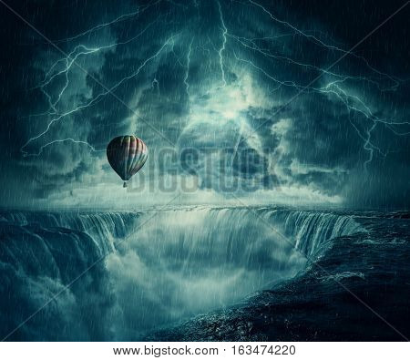 Inspirational imaginary view scary landscape as a hot air balloon fly over the chasm of a foggy waterfall below a dark stormy sky.