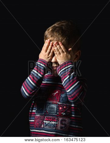 Portrait of scared boy covering eyes with his hands over a black background