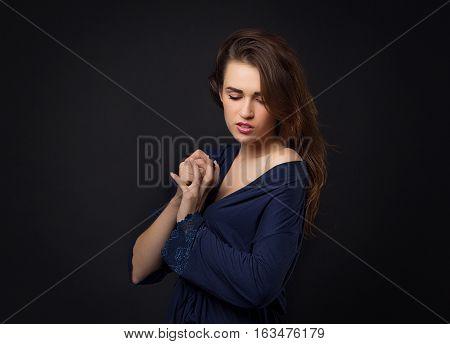 Girl In Blue Peignoir With Bare Shoulder. Dark Background