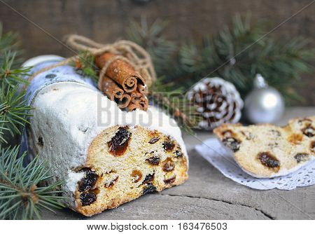 Christmas stollen with marzipan, berries and cinnamon.Traditional German festive baking.Stollen Christmas cake.Soft selective focus.Copy space.