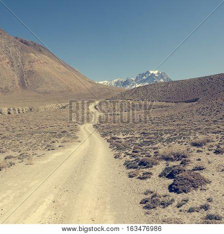Dirt road through arid mountain wastelands. Annapurna circuit Trek in Nepal.