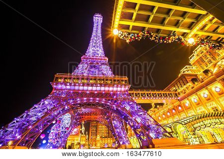 Macau, China - December 8, 2016: Perspective view of pink Macau Eiffel Tower, icon of The Parisian, a luxury Resort Hotel Casino in Cotai Strip owned by Las Vegas Sands, shines bright at night.