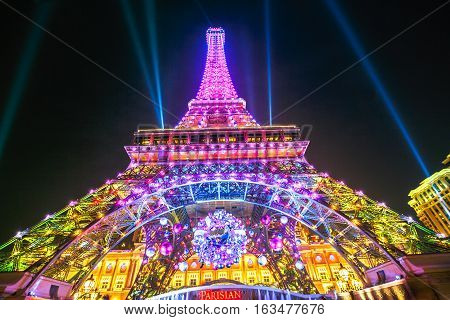 Macau, China - December 8, 2016: Perspective view of colorful Macau Eiffel Tower, icon of The Parisian, a luxury Resort Hotel Casino in Cotai Strip while shines bright at night during the laser show.