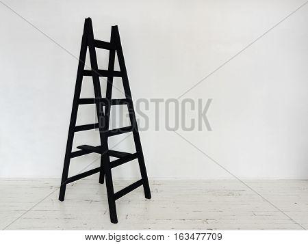 Black wooden stepladder in interior Black stepladder standing in three quarters in white room with wooden floor