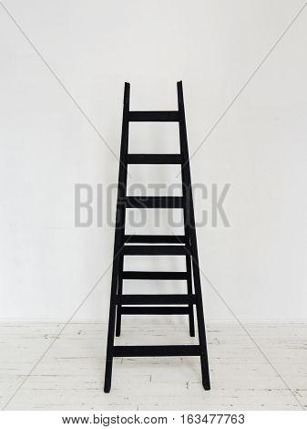 Black wooden stepladder in interior Black stepladder standing in white room with wooden floor